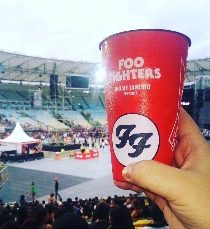 Mão segurando copo vermelho do Foo Figthers de frente para o palco